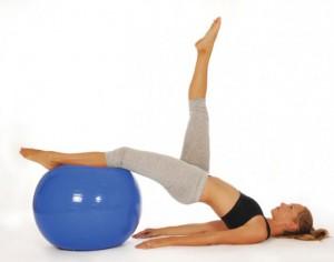 Em exibição, praticante de pilates fazendo exercício com a bola