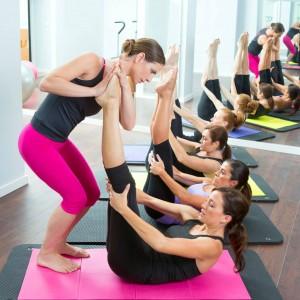 Instrutor de Pilates auxiliando a praticante