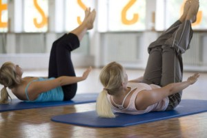 Em detalhes, duas praticantes de pilates durante um exercício