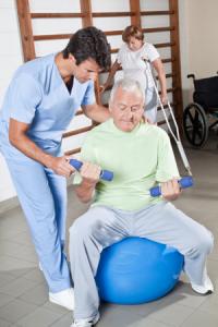 Em detalhes, idoso sendo auxiliado durante uma sessão de fisioterapia do pilates